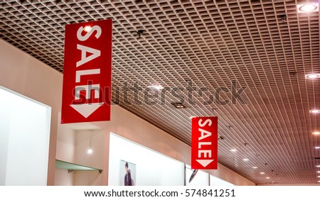 red vertical sale posters with white letters hang from grid ceiling in big shop in sale
