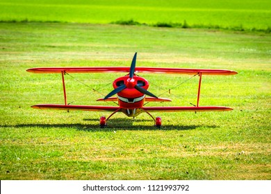 Red veteran plane ready to take off from a green meadow in the summer