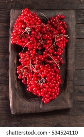 red viburnum on a old wooden background, healthy red berries.
