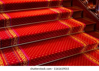 Red Victorian carpet, on a mahogany staircase