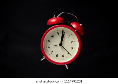 Red vintage alarm clock floating in the dark with blackboard background