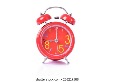 Red vintage alarm clock isolated on white