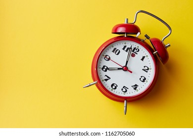Red vintage alarm clock on yellow background. Alarm clock with place for text. Back to school concept.