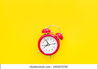 Red vintage alarm clock on a yellow background, top view
