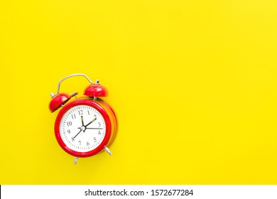 Red vintage alarm clock on a yellow background