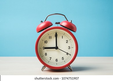 Red vintage alarm clocks on wooden table and light blue background wall