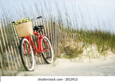 Rotes Vintage-Fahrrad mit Korb und Blumen auf hölzernem Zaun am Strand.