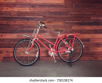 Red vintage bicycle with retro wood wall background , copy space