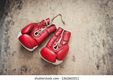 Red vintage boxing gloves on a wooden background