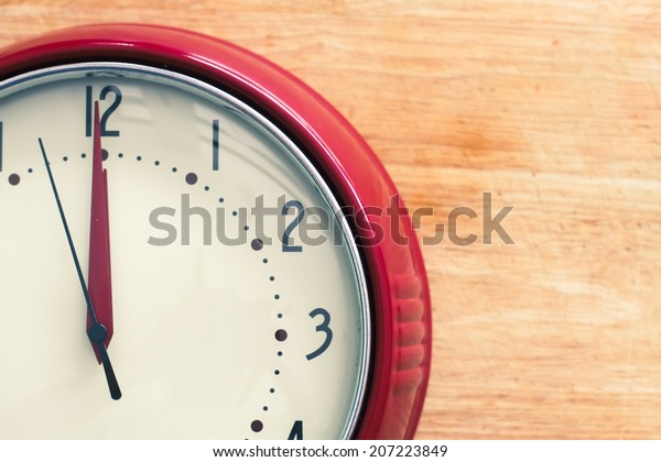 Red vintage clock about to strike 12 midnight or midday, possibly conceptual of New Year.