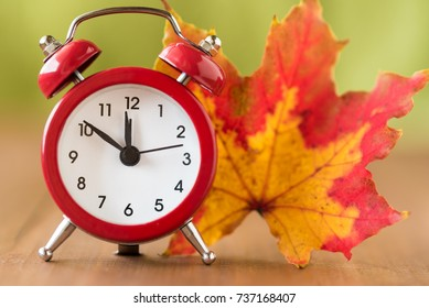 Red vintage clock and mable leaf. Autumn time change