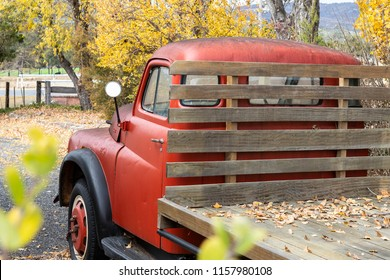 Red Vintage Farm Truck with Autumn Trees in Background