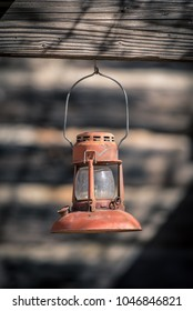 Red vintage kerosene lantern hanging in front of weathered wooden clap boards
