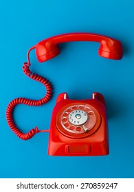 red vintage phone with handset off the hook, on blue background