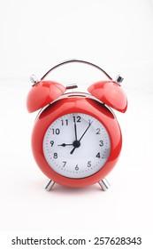 red vintage retro alarm clock on white background