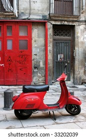 Red vintage scooter parked in the streets of Barcelona