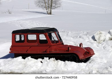 Red vintage snow plow or snowplough in snow, Plateau of Glieres, Savoy
