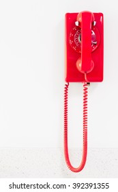 Red vintage telephone hanging on white wall