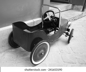 Red vintage toy car near entrance to the house. Back and side view. Aged photo. Black and white.