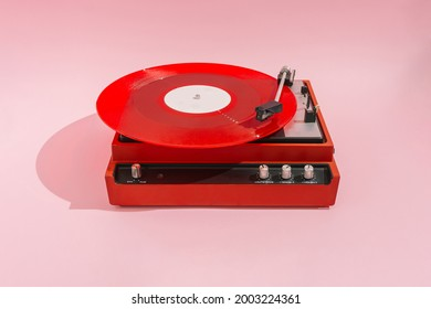 Red vinyl LP on red record player with light pink background. Minimal party concept.