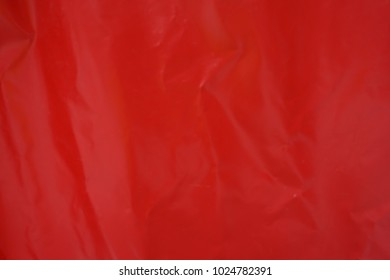 Red vinyl material. Used Texture with pleats, waves. Crumpled surface. Close up