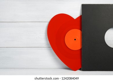 Red vinyl record for a turntable a heart shaped player with a grey cover on a white wooden background of their boards. Listening to Christmas songs. Valentine's Day, Christmas. Ready picture for your
