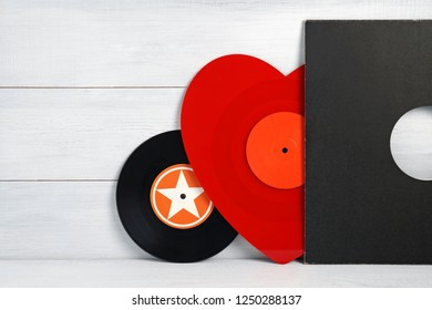Red vinyl record for a turntable a heart shaped player with a grey cover on a white wooden background of their boards. Listening to Christmas songs. Valentine's Day, Christmas. Black vinyl record