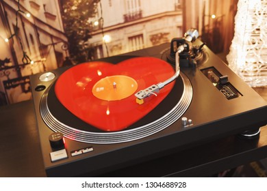 Red vinyl in the shape of a heart on a festive background with bokeh lights. A ray of light on a piece of vinyl. Sound technology for DJ mix and turntable. Stylus with needle. Valentine's Day. Love