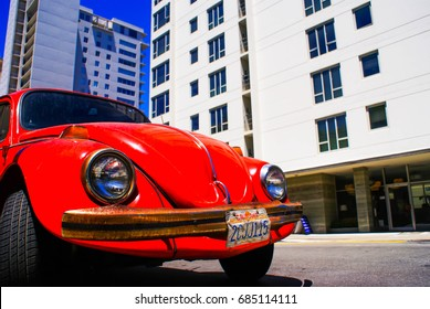 A Red Volkswagen Beetle with a California number plate (license plate) sits parked on a street in San Francisco - San Francisco, USA (30 June 2014)