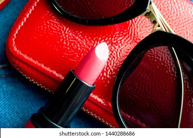 red wallet, red lipstick and sunglass on jeans pants