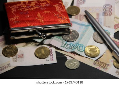 Red wallet on the background of banknotes and coins. Finance and Investment