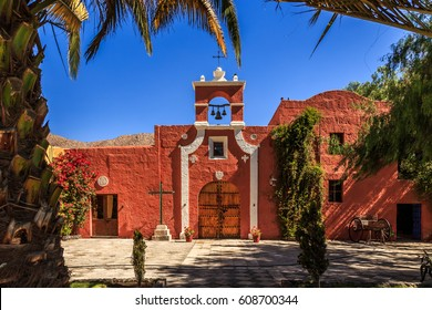 Red walls of Spanish catholic chapel with palms, trees and flowers, Arequipa, Peru