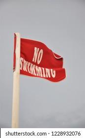 Red warning flag at the beach, No Swimming!