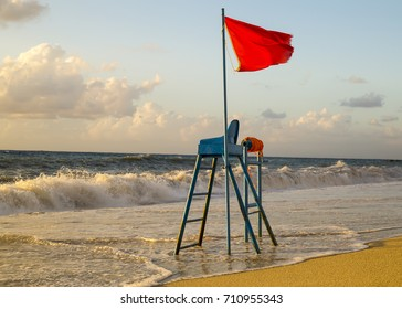 Red warning flag flapping in the wind on the beach at storm / Lifeguard tower on the beach