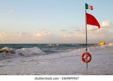 Red warning flag and Italy flag flapping in the wind on the beach at storm. Lifeguard place with lifebuoy on the beach in Italy, Calabria region