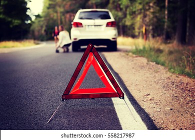 Red warning triangle and broken car in the middle of forrest