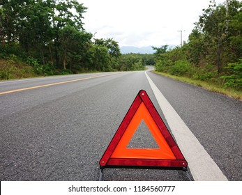 Red warning triangle on the road sign with cloudy day