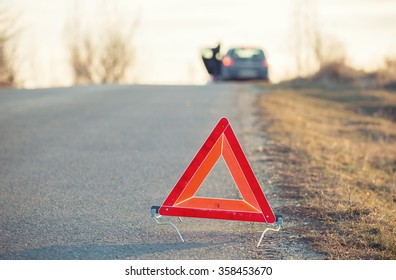 Red warning triangle on a road with a broken down car in the background in sunset light