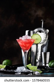 Red Watermelon alcoholic cocktail with vodka, juice, lime and crushed ice, metal bar tools, dark background