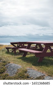 Red weathered picnic table with blue skies