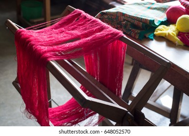 Red weaving yarn hung on a handloom