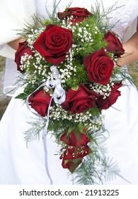 Red wedding bouquet at bride's hands