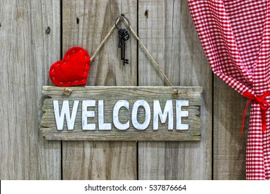 Red welcome sign with  country fabric holiday heart with black iron house keys hanging by red and white gingham curtain on antique rustic wood door; Valentine's Day background
