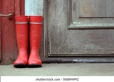 Red wellies outside of old house. Horizontal image with lots of copy space.