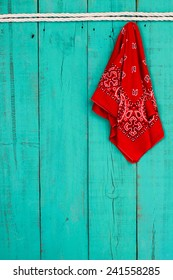 Red western bandanna or handkerchief hanging on blank antique teal blue rustic wooden background with white rope border