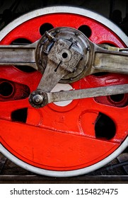 Red wheel of old steam locomotive, closeup shot, industrial background