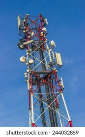 Red and white antenna structure over blue sky
