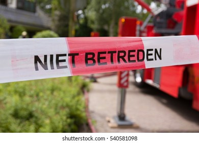 "a red and white barrier tape with dutch words ""niet betreden ""on it which means: do not enter"". To keep unauthorized people out of the scene"