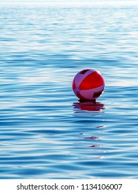 a red and white beach ball floats out and away on lake Michigan in the USA