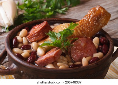 red and white beans with chicken legs and grilled sausages in a bowl on the table. close up horizontal
